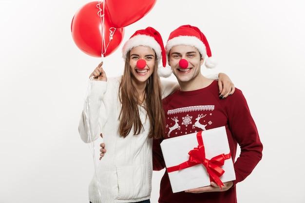 De jonge kaukasische giften en de ballon die van de paarholding grappig gezicht op kerstmis maken.