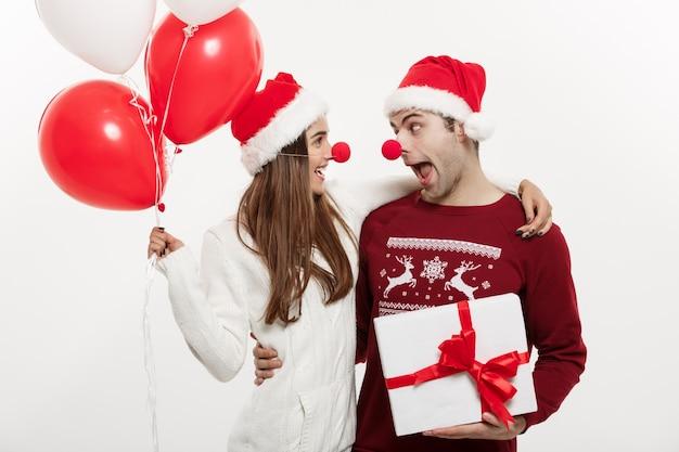 De jonge kaukasische giften van de paarholding, champnage en ballon die grappig gezicht op kerstmis maken.