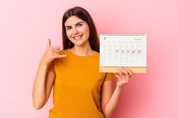 De jonge kaukasische kalender van de vrouwenholding die op roze muur wordt geïsoleerd die een mobiel telefoongesprekgebaar met vingers toont.
