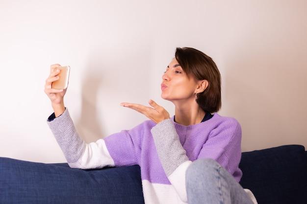 De jonge kaukasische meisjesvrouw in slaapkamer op bank bekijkt mobiele telefooncamera