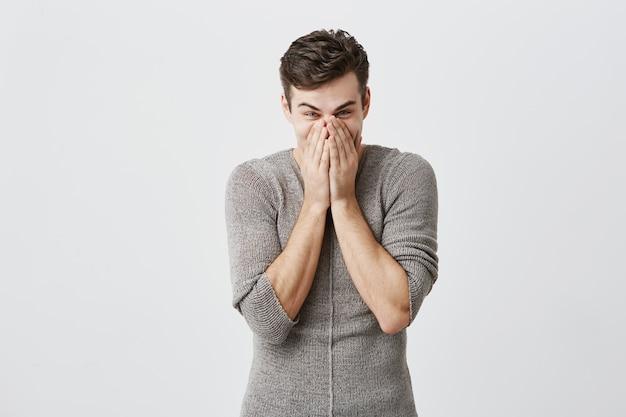 De jonge kaukasische mens die afgeluisterde ogen heeft, behandelt mond kijkt in verschrikking, emotioneel of bang na het horen van schokkend nieuws op radio, geïsoleerd. negatieve emoties