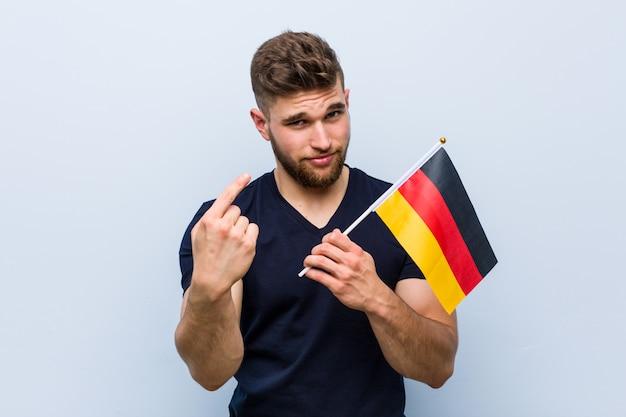 De jonge kaukasische mens die een vlag houden die van duitsland met vinger op u richten alsof uitnodigend dichter komt.