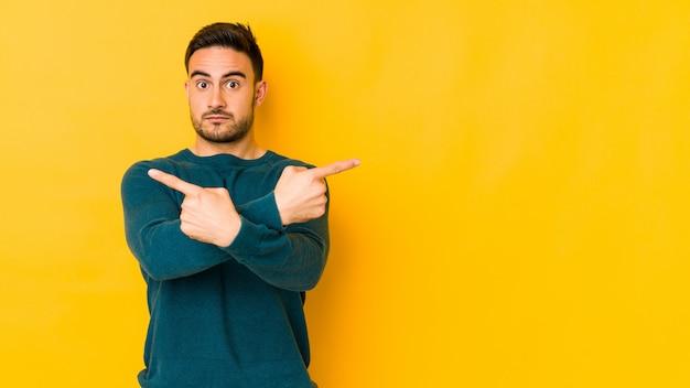 De jonge kaukasische mens die op gele bakground zijwaarts punten wordt geïsoleerd, probeert om tussen twee opties te kiezen.