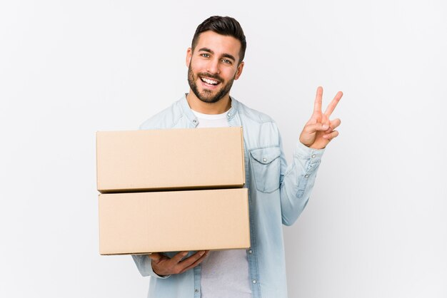 De jonge kaukasische mens die zich naar een nieuw huis beweegt isoleerde blij en onbezorgd tonend een vredessymbool met vingers.