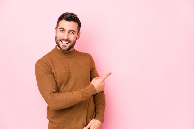 De jonge kaukasische mens tegen een roze muur isoleerde opzij glimlachend en richtend, tonend iets op lege ruimte.