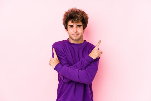 De jonge kaukasische mens tegen een roze muur isoleerde zijdelings punten, probeert tussen twee opties te kiezen.