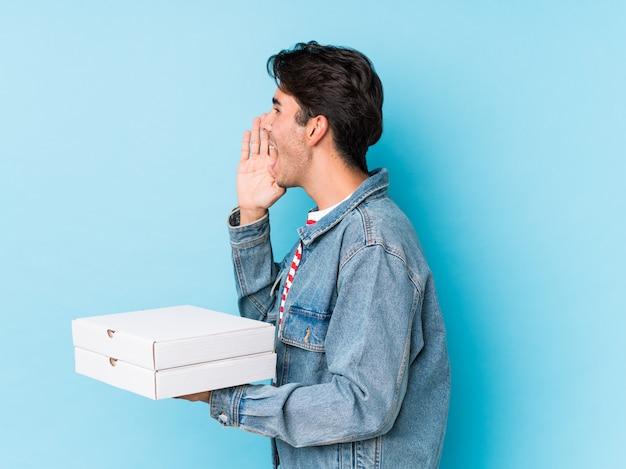 De jonge kaukasische pizza's van de mensenholding geïsoleerd schreeuwend en houdend palm dichtbij geopende mond.