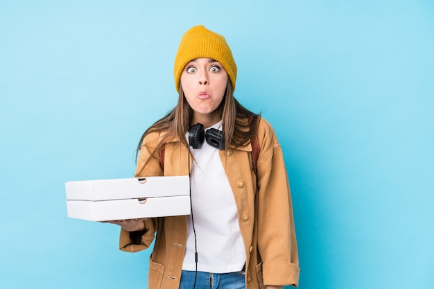De jonge kaukasische pizza's van de vrouwenholding haalt schouders en open ogen op verward.