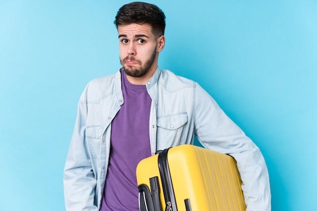 De jonge kaukasische reizigersmens die een koffer geïsoleerd houden haalt schouders op en open ogen verward.