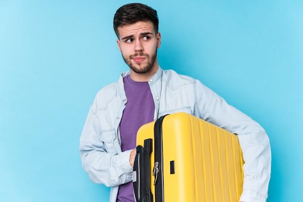 De jonge kaukasische reizigersmens die een koffer verward houden, voelt twijfelachtig en onzeker.