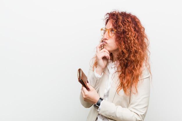 De jonge kaukasische roodharigevrouw die een portefeuille houden ontspande het denken over iets bekijkend een exemplaarruimte.