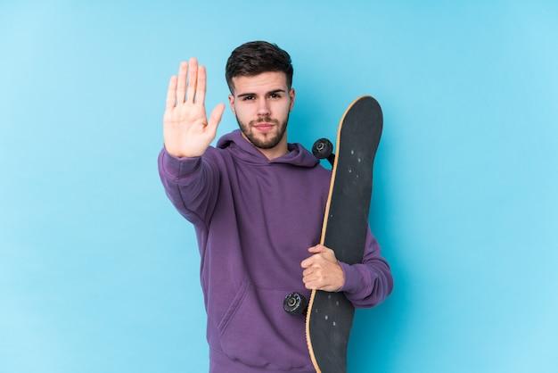 De jonge kaukasische schaatsermens isoleerde status met uitgestrekte hand die eindeteken tonen, die u verhinderen.