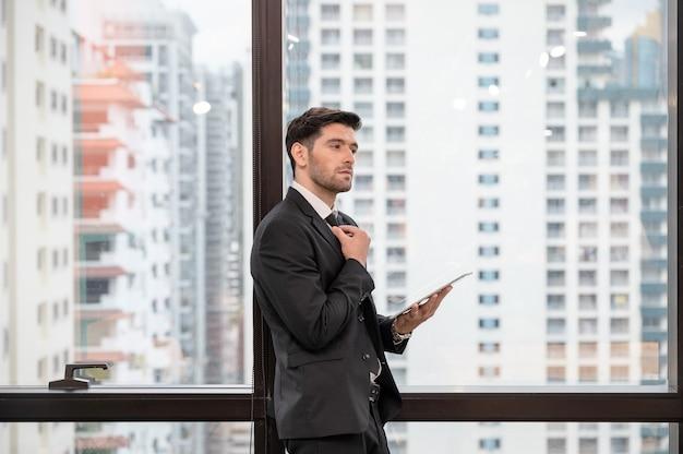 De jonge kaukasische stropdas en de tablet van de zakenmanholding in het bureau