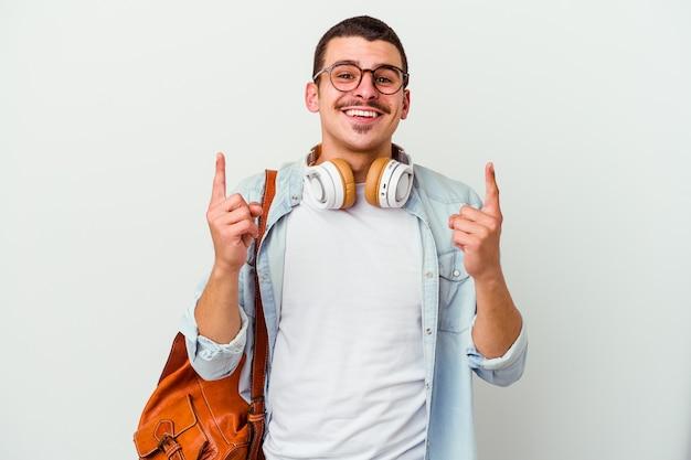 De jonge kaukasische studentenmens die aan muziek luistert die op witte muur wordt geïsoleerd, geeft aan met beide voorvingers omhoog het tonen van een lege ruimte