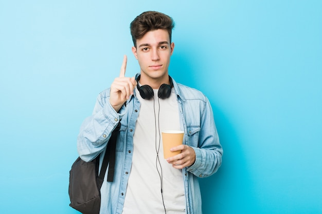 De jonge kaukasische studentenmens die haalt koffie weg tonen die nummer één met vinger tonen.