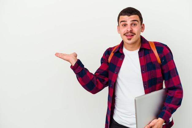 De jonge kaukasische studentenmens die laptop houdt die op witte muur wordt geïsoleerd, houdt exemplaarruimte op een palm, houdt hand over wang