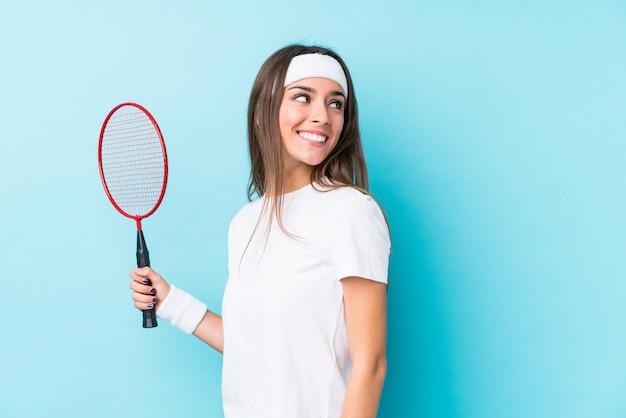 De jonge kaukasische vrouw die badminton speelt kijkt opzij glimlachend, vrolijk en aangenaam.