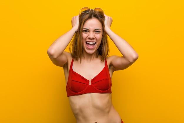 De jonge kaukasische vrouw die bikini en zonnebril draagt lacht vreugdevol houdend handen op hoofd. geluk .