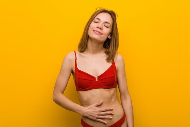 De jonge kaukasische vrouw die bikini en zonnebril draagt raakt buik, glimlacht zacht, het eten en tevredenheidsconcept.
