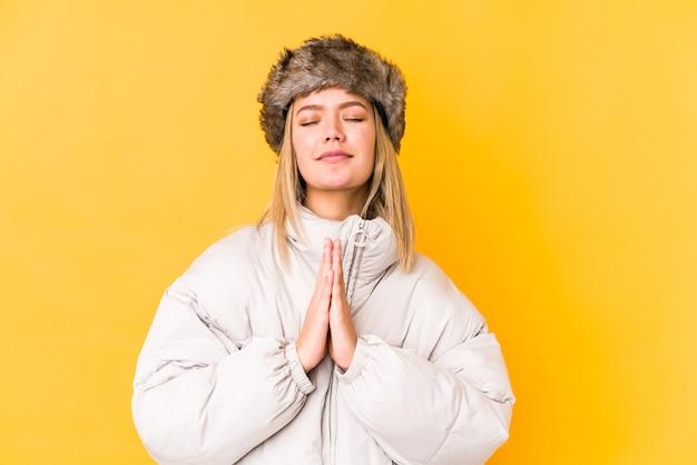 De jonge kaukasische vrouw die de winterkleren geïsoleerde hand in hand draagt, bidt dichtbij mond, voelt zich zelfverzekerd.
