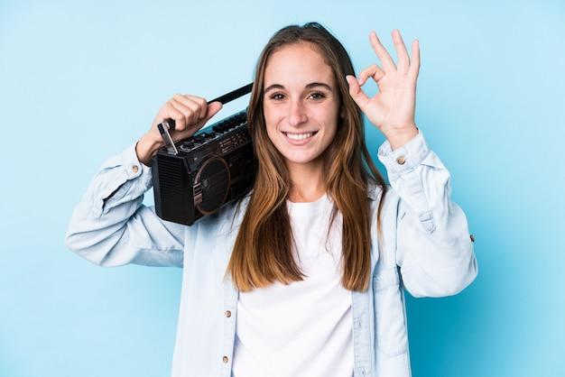 De jonge kaukasische vrouw die een cassete houden isoleerde vrolijk en zeker tonend ok gebaar.