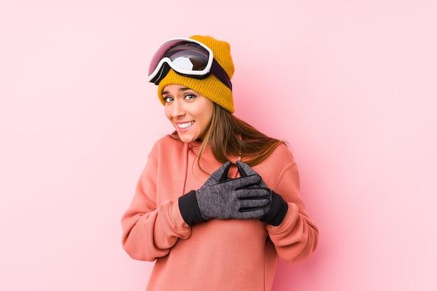 De jonge kaukasische vrouw die een geïsoleerde skikleren draagt, heeft vriendelijke uitdrukking, die palm aan borst drukt. liefde concept.