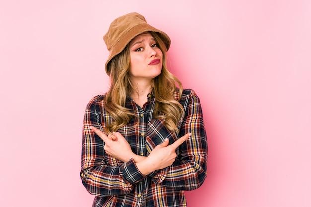 De jonge kaukasische vrouw die een hoed geïsoleerde punten zijdelings draagt, probeert te kiezen tussen twee opties.