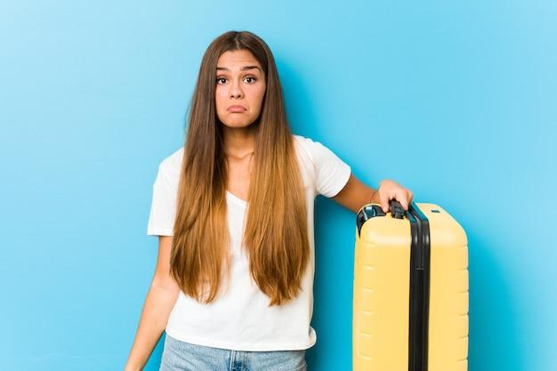 De jonge kaukasische vrouw die een reiskoffer houdt, haalt schouders op en opent verwarde ogen.