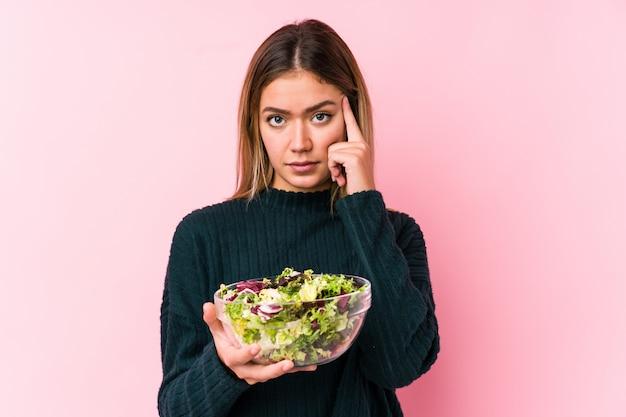 De jonge kaukasische vrouw die een salade geïsoleerd houden richtend zijn tempel met vinger, denken, concentreerde zich op een taak.