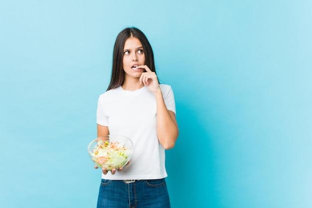 De jonge kaukasische vrouw die een salade houdt ontspande denkend over iets bekijkend een lege ruimte.