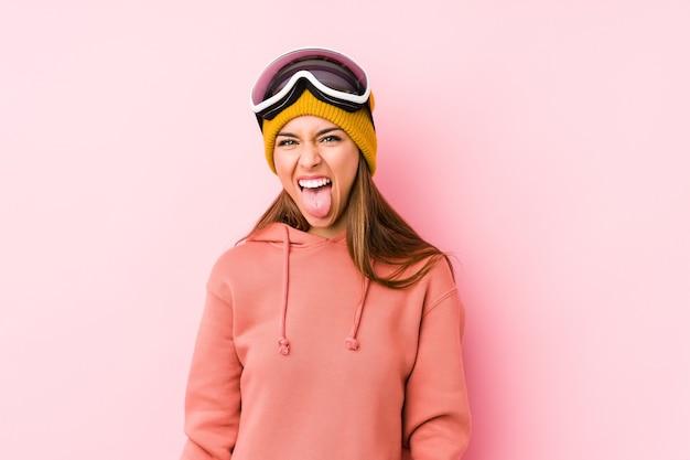 De jonge kaukasische vrouw die een skikleren draagt isoleert grappige en vriendschappelijke tong uitsteekt.