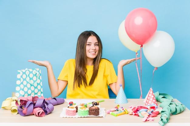 De jonge kaukasische vrouw die een verjaardag organiseert maakt schaal met wapens, voelt gelukkig en zeker.