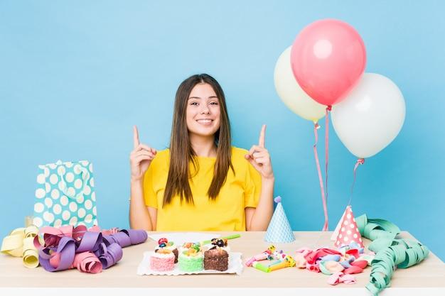 De jonge kaukasische vrouw die een verjaardag organiseert wijst op met beide voorvingers die omhoog een lege ruimte tonen.
