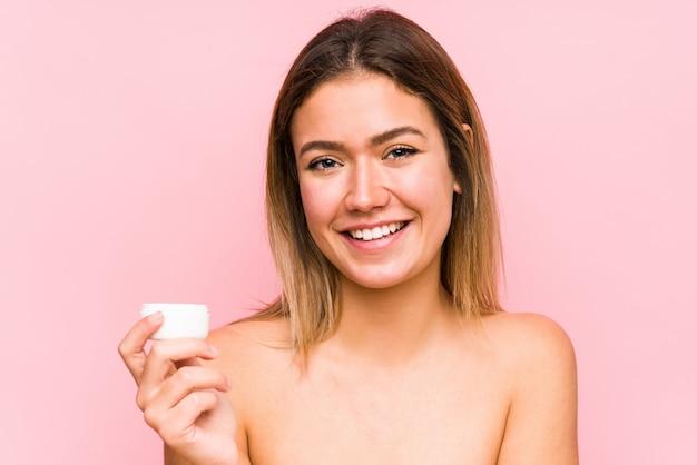 De jonge kaukasische vrouw die een vochtinbrengende crème houdt isoleerde gelukkig, glimlachend en vrolijk.