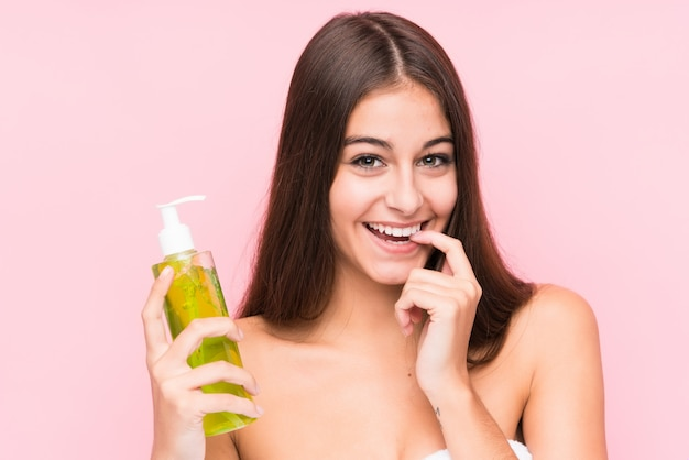 De jonge kaukasische vrouw die een vochtinbrengende crème met aloë vera houden ontspande het denken over iets