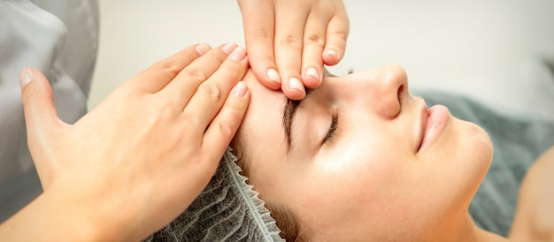 De jonge kaukasische vrouw die gezichtsmassage door de handen van de schoonheidsspecialist ontvangt in de medische salon van de kuur