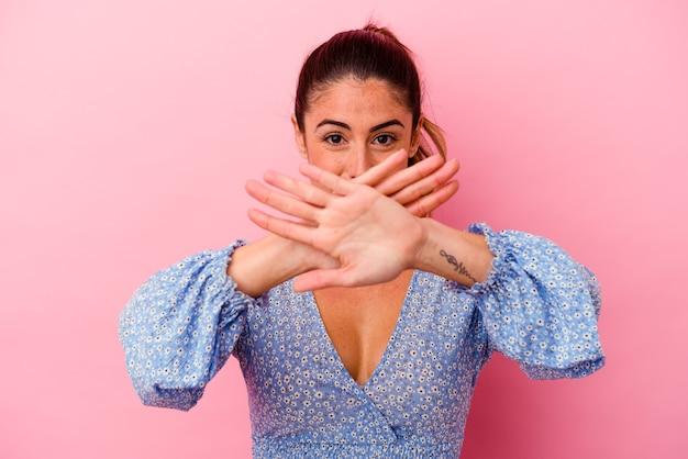 De jonge kaukasische vrouw die op roze zijwaartse punten wordt geïsoleerd als achtergrond, probeert om tussen twee opties te kiezen.