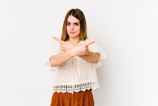 De jonge kaukasische vrouw die op witte muur wordt geïsoleerd richt zijwaarts, probeert om tussen twee opties te kiezen.