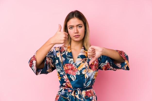 De jonge kaukasische vrouw die pyjama's dragen die duimen tonen en duimen neer, kiest concept moeilijk