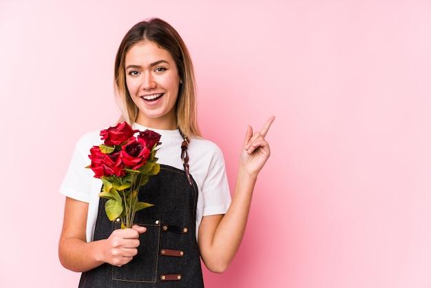 De jonge kaukasische vrouw die rozen geïsoleerd houden glimlachend vrolijk richtend met weg wijsvinger.
