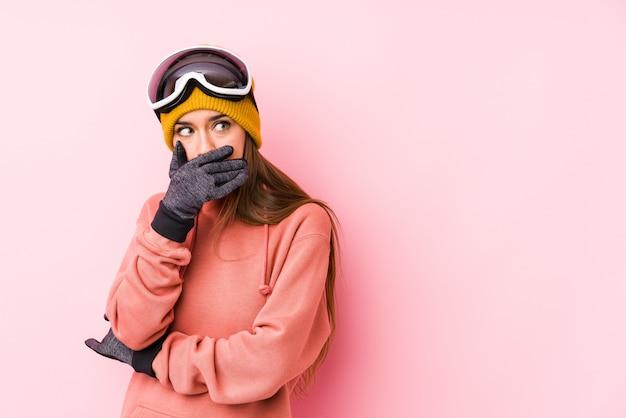 De jonge kaukasische vrouw die ski draagt kleedt geïsoleerde het nadenkende kijken aan een exemplaarruimte die mond behandelen met hand.