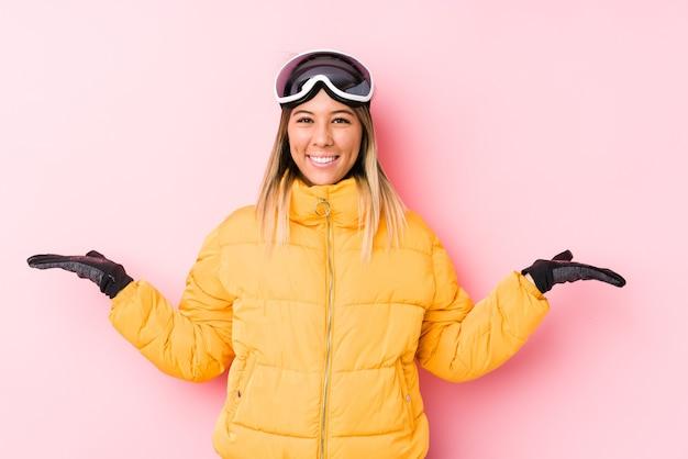 De jonge kaukasische vrouw die skikleren in een roze ruimte draagt, maakt schaal met wapens, voelt zich gelukkig en zelfverzekerd.