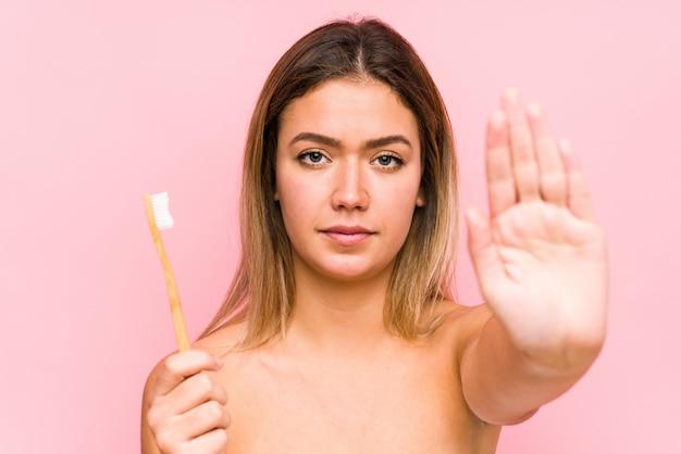 De jonge kaukasische vrouw die tanden houden poetst geïsoleerde status met uitgestrekte hand die eindeteken tonen, die u verhinderen.
