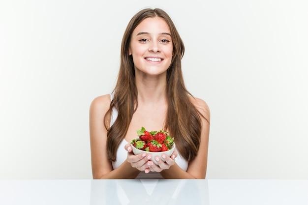 De jonge kaukasische vrouw holdingstrawberries kom gelukkig, glimlachend en vrolijk.