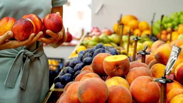 De jonge kaukasische vrouw kiest een rijpe nectarines bij supermarkt. close-up van vrouwelijke handen neemt perziken uit de plank.