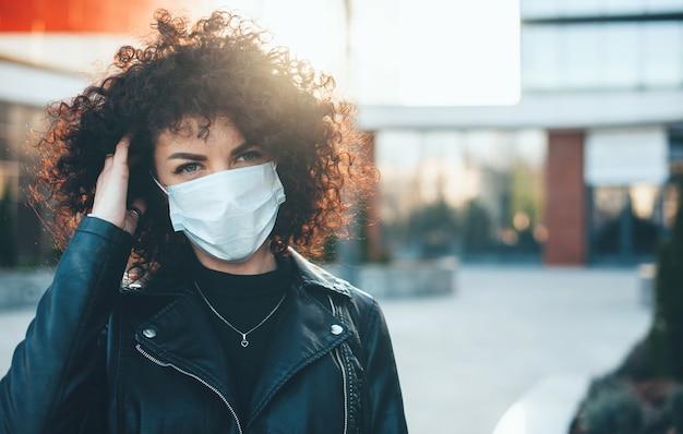 De jonge kaukasische vrouw met krullend haar en zwart leerjasje draagt beschermend masker