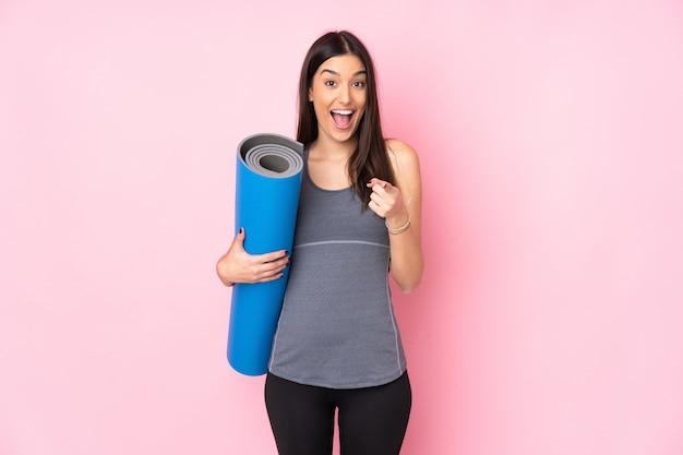 De jonge kaukasische vrouw met mat op roze muur richt vinger op u