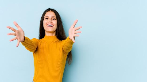 De jonge kaukasische vrouw op blauwe muur voelt zeker het geven van een omhelzing