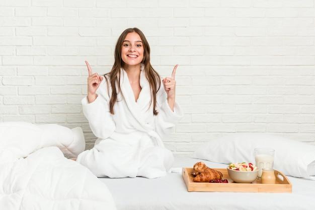 De jonge kaukasische vrouw op het bed geeft met beide voorvingers op die lege ruimte tonen.