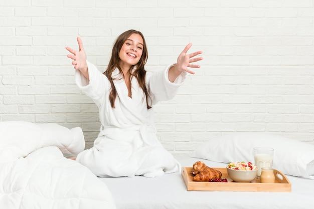 De jonge kaukasische vrouw op het bed voelt zeker het geven van een knuffel aan.
